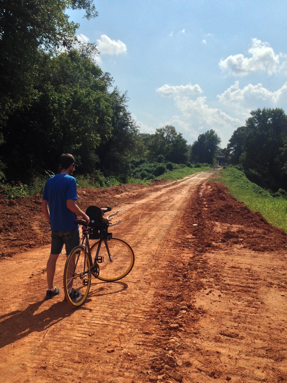 man standing and holding road bike on dirt road near trees