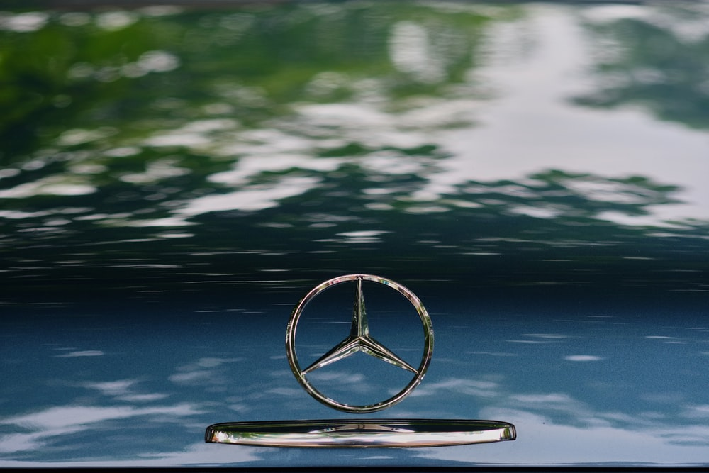 silver-colored Mercedes-Benz emblem on focus photography