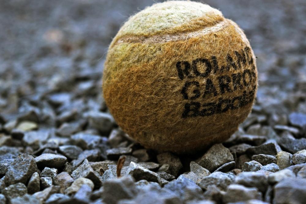 selective focus photography of tennis ball on rocks