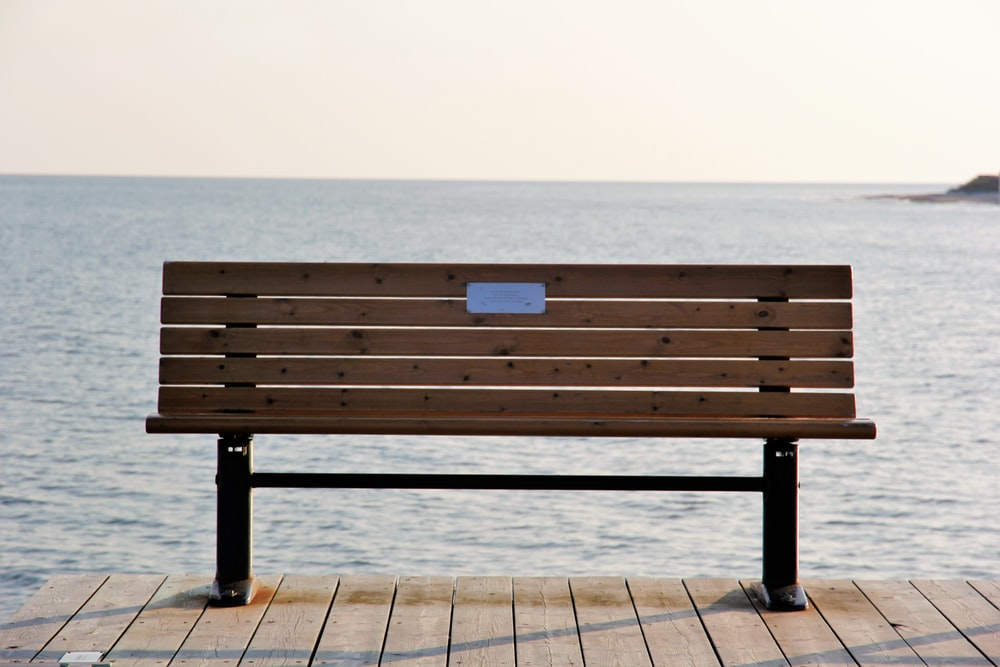 brown bench on dock during daytime