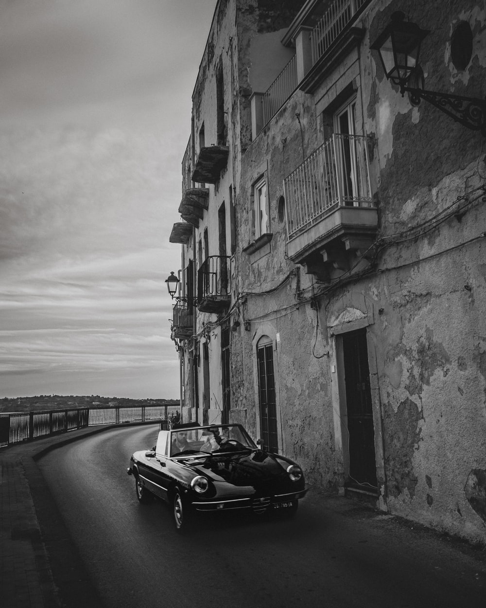 grayscale photo of car beside building