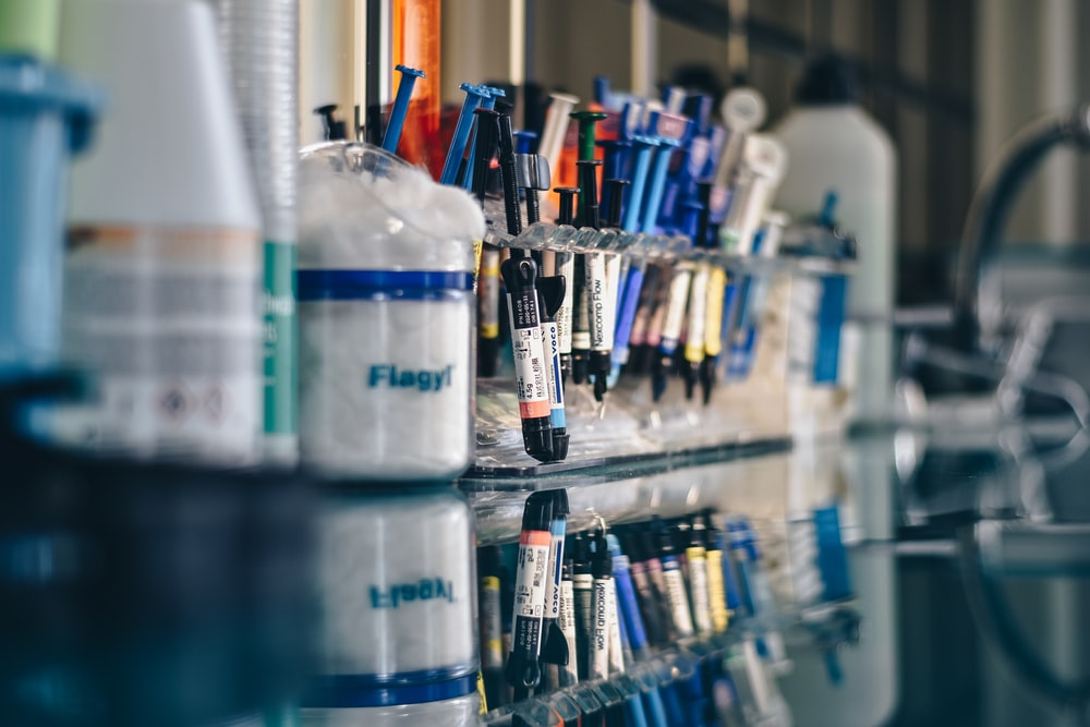 assorted-color syringes on clear glass rack