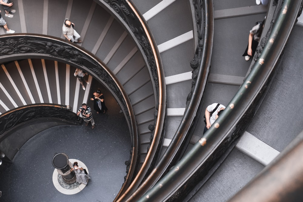 top-view photography of people walking down on spiral stairs