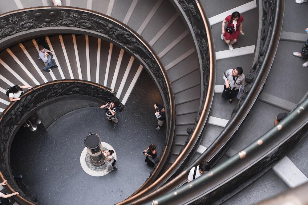 people walking on spiral stairs inside building