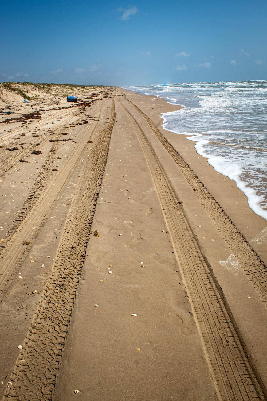 vehicle tires on seashore during daytime