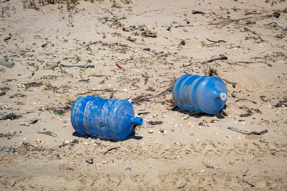 two blue plastic carboys on seashore