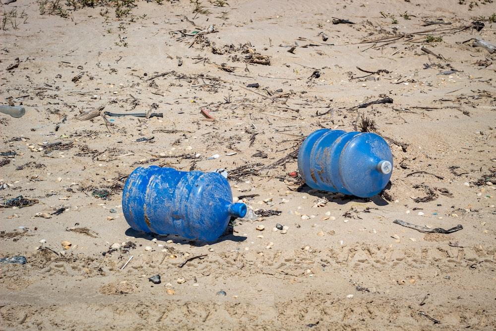two blue plastic carboys on seashore