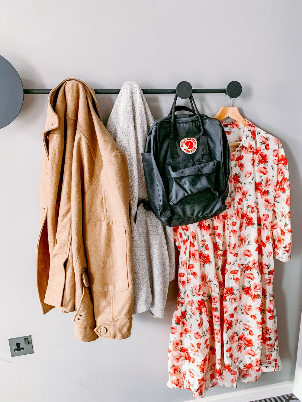 coat, sweater, backpack, and floral dress hanging on wall hanger