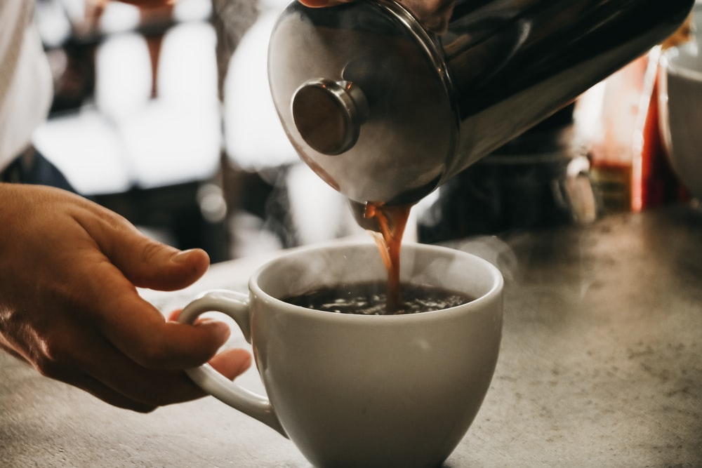 person pouring coffee in white ceramic cup