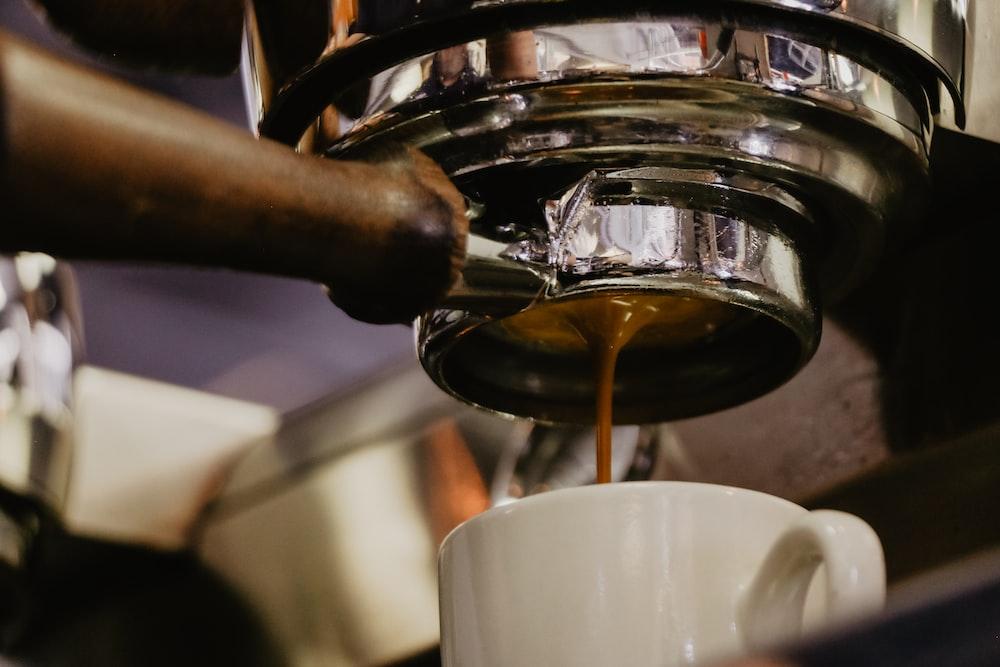 white ceramic mug under espresso maker