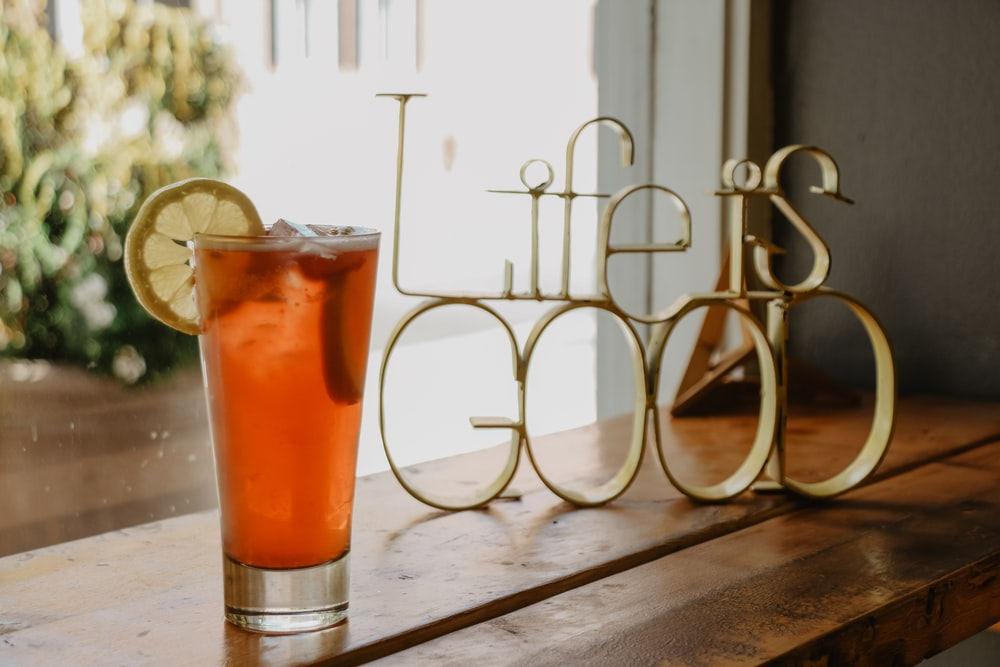 glass of drink beside life is good decorative letters