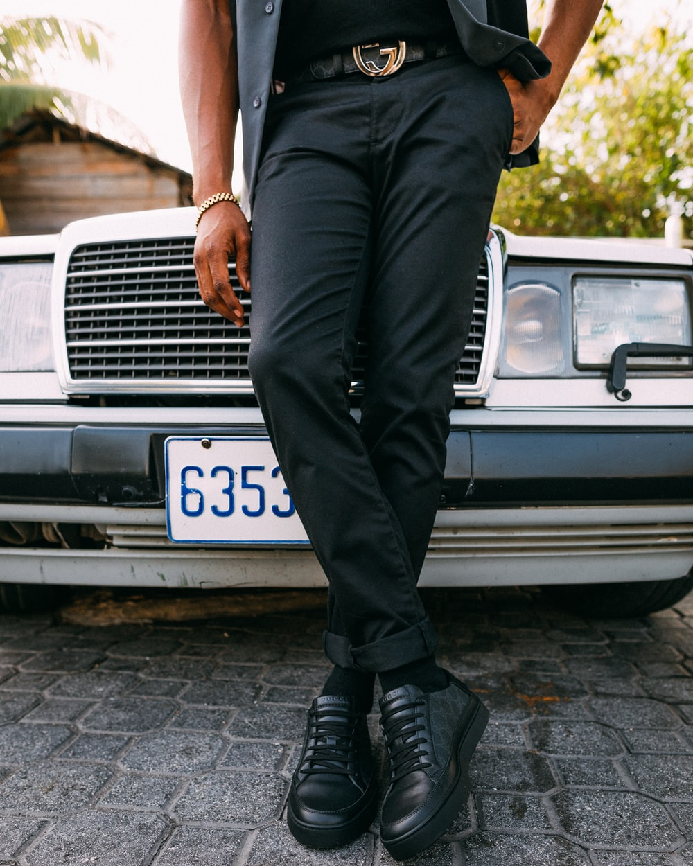 person wearing black dress pants leaning on black vehicle