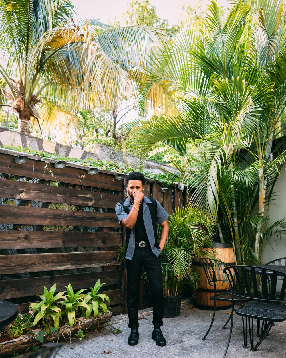 man standing near wooden wall at patio