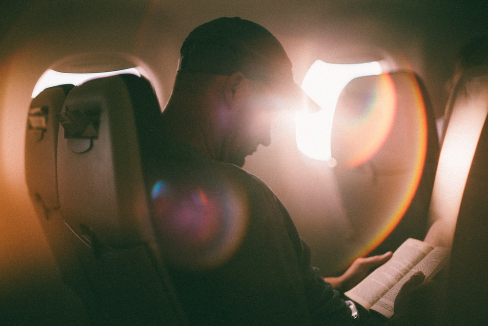 man sitting and reading book inside airplane