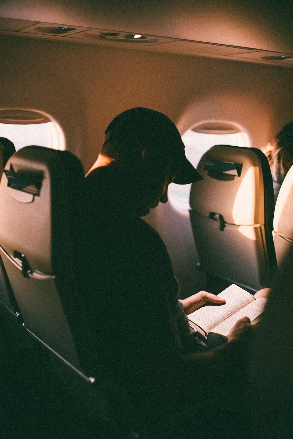 man sitting inside plane reading book