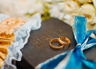 gold-colored wedding rings on Bible scripture