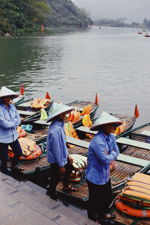 three men standing beside boats