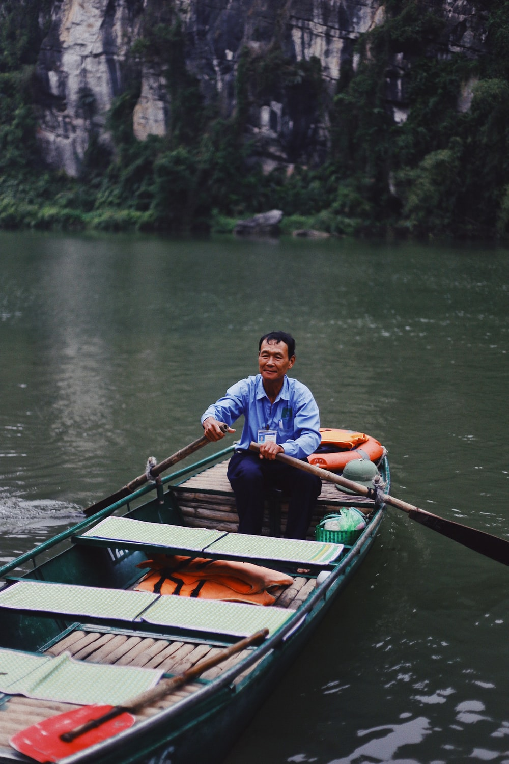 man sitting on boat and paddling