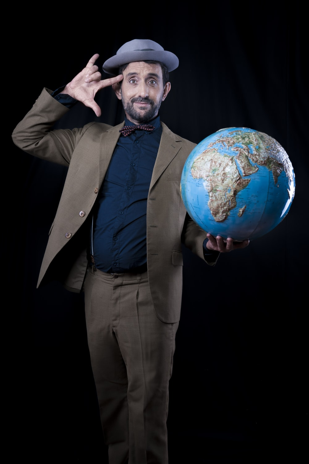 man in brown suit jacket and dress pants holding planet earth toy
