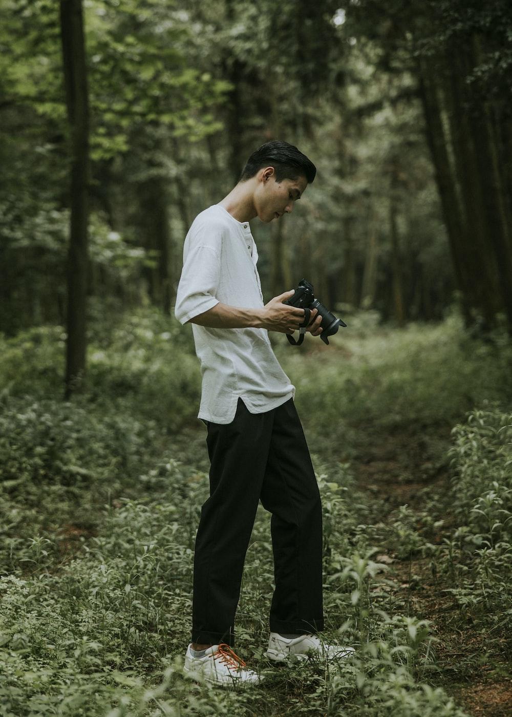 man standing black DSLR camera