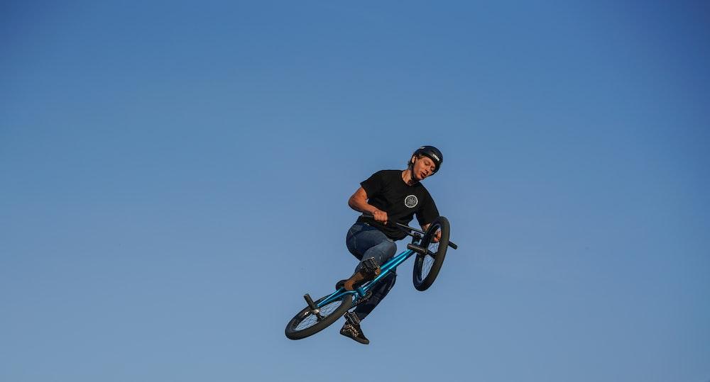 man riding BMX bike under blue sky
