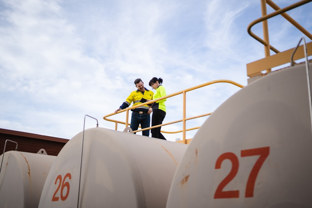 two employees on top of 26 tank number