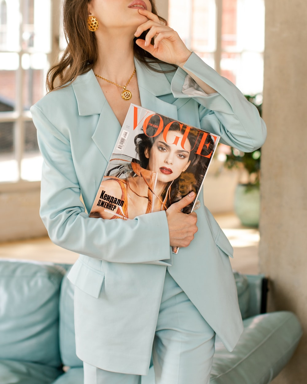 woman wearing blazer holding Vogue magazine
