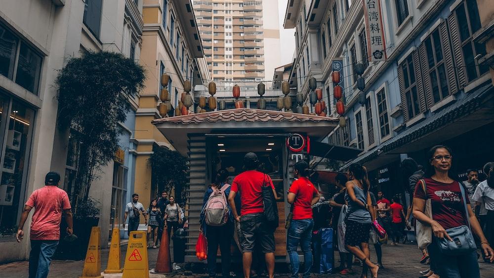 group of people standing near buildings ]