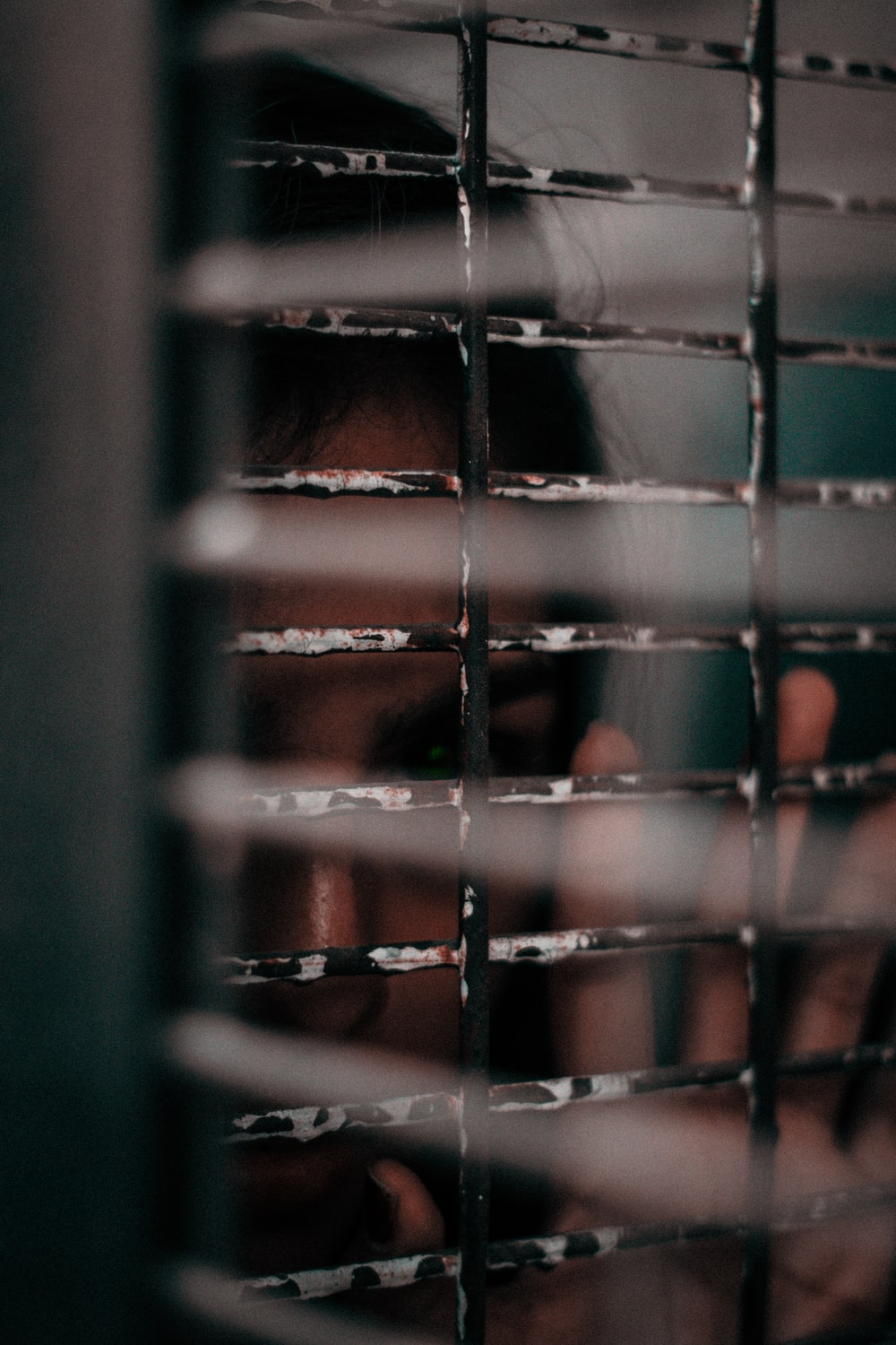 woman looking from a window grille