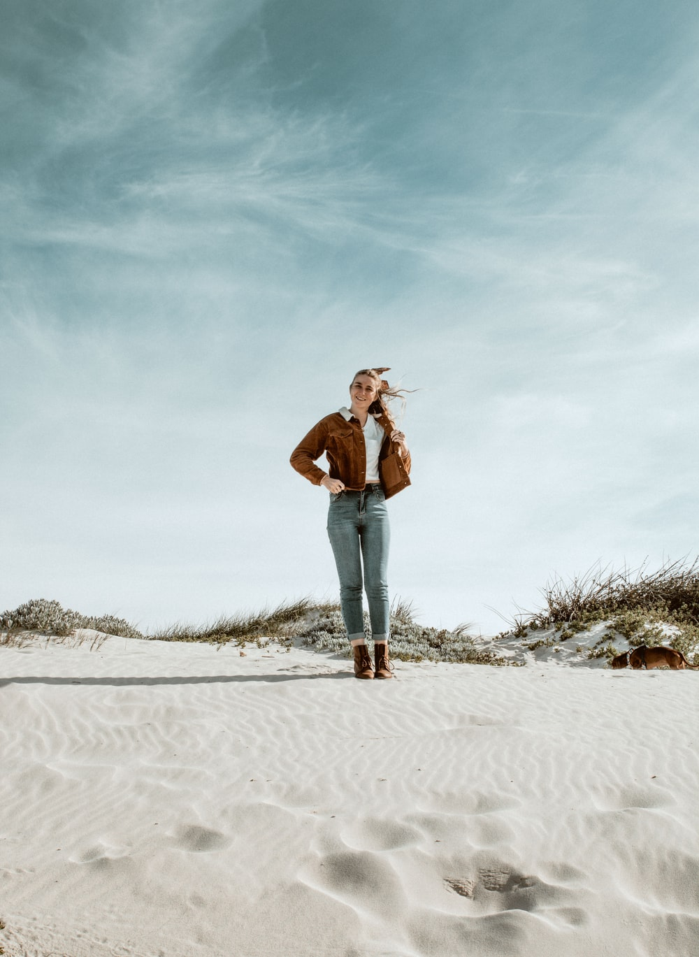 woman in brown coat standing on focus photography