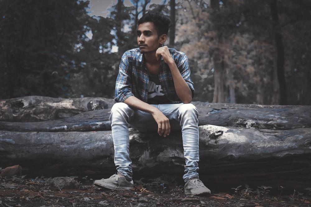 man wearing sport shirt sitting on log
