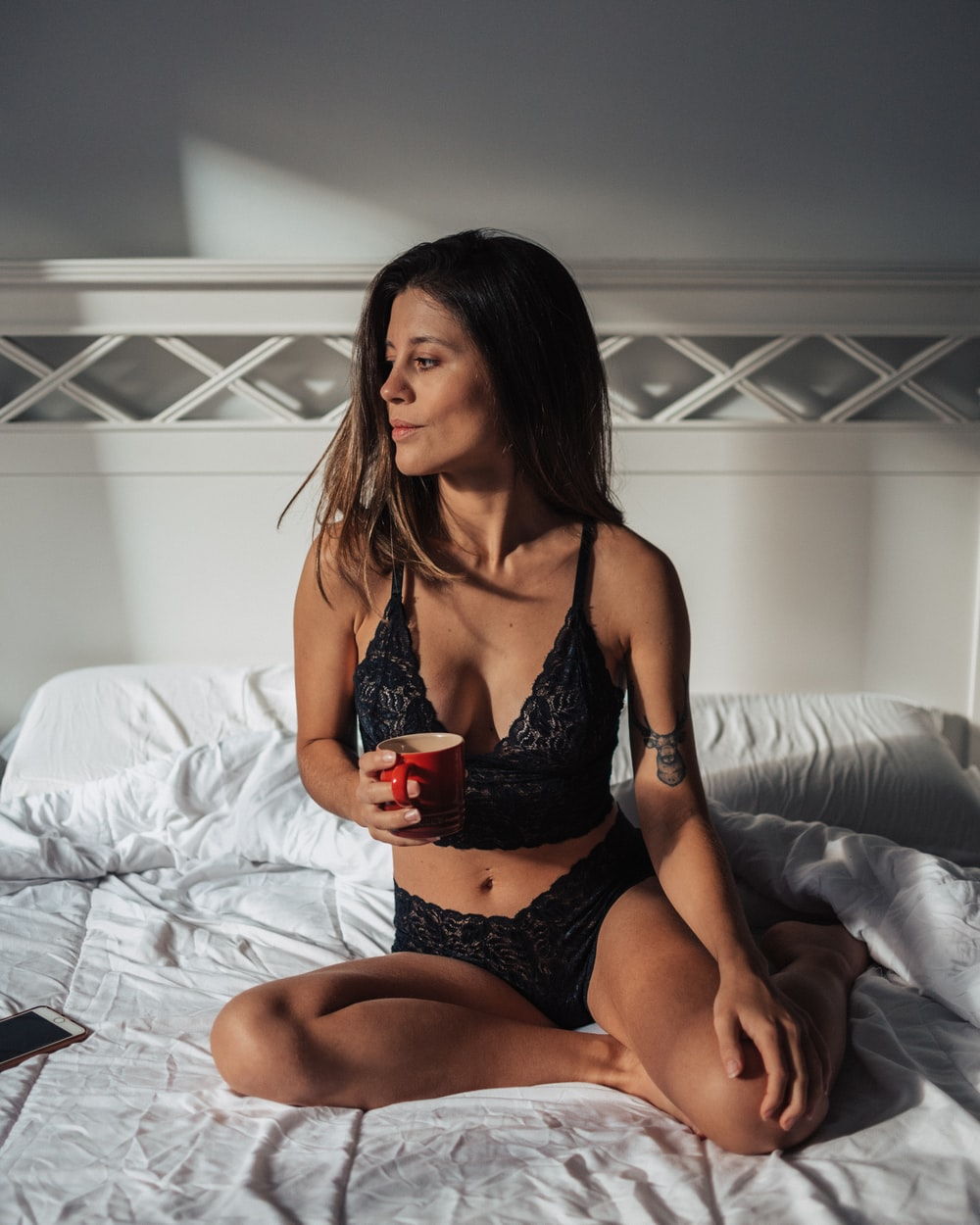 woman wearing black bra and panties sitting on bed