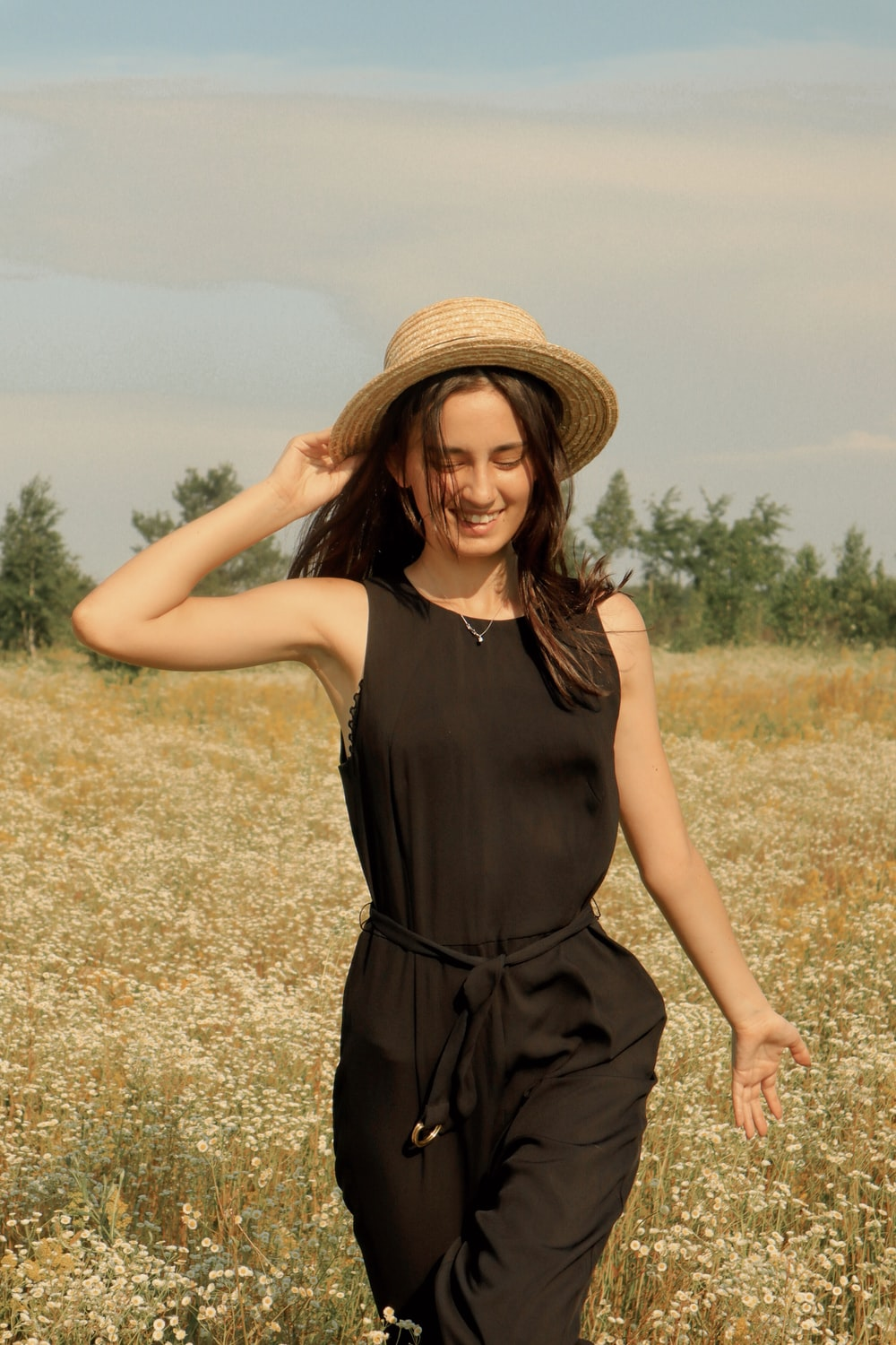 woman wearing black jumpsuit and sunhat