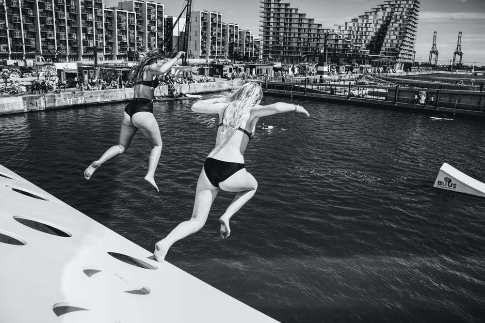two women jumps on water