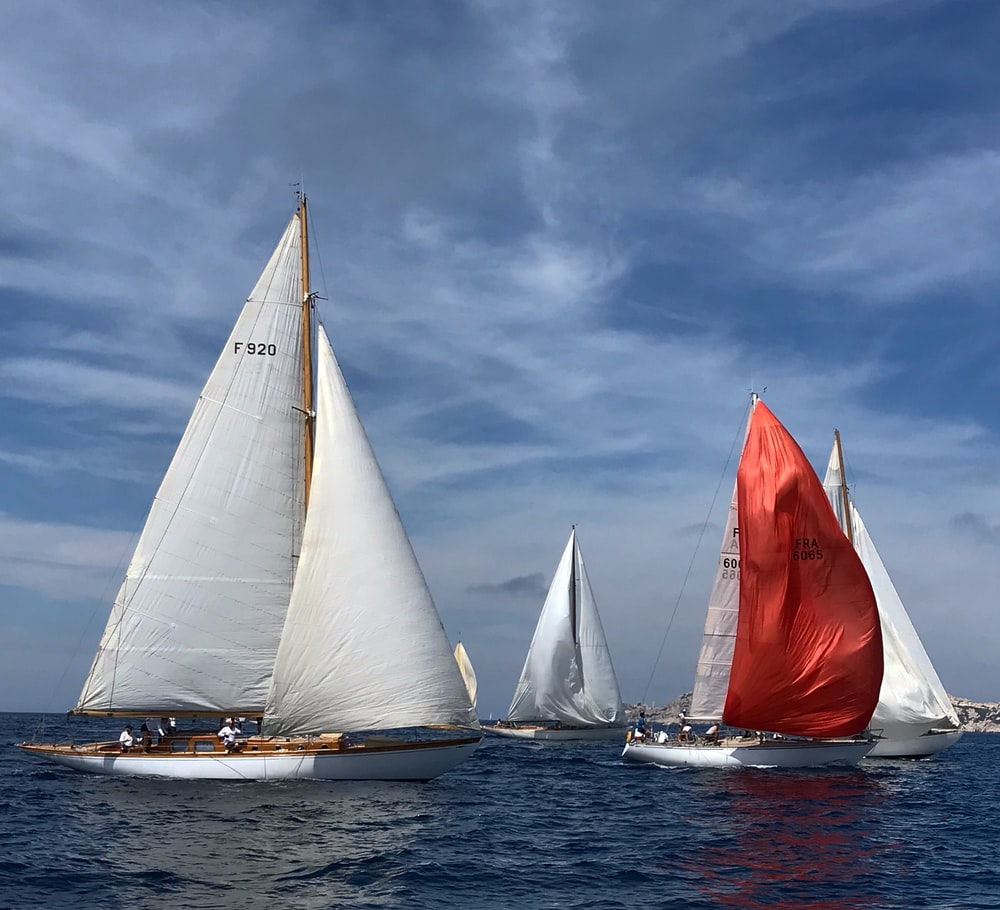 three white-and-red sail boats