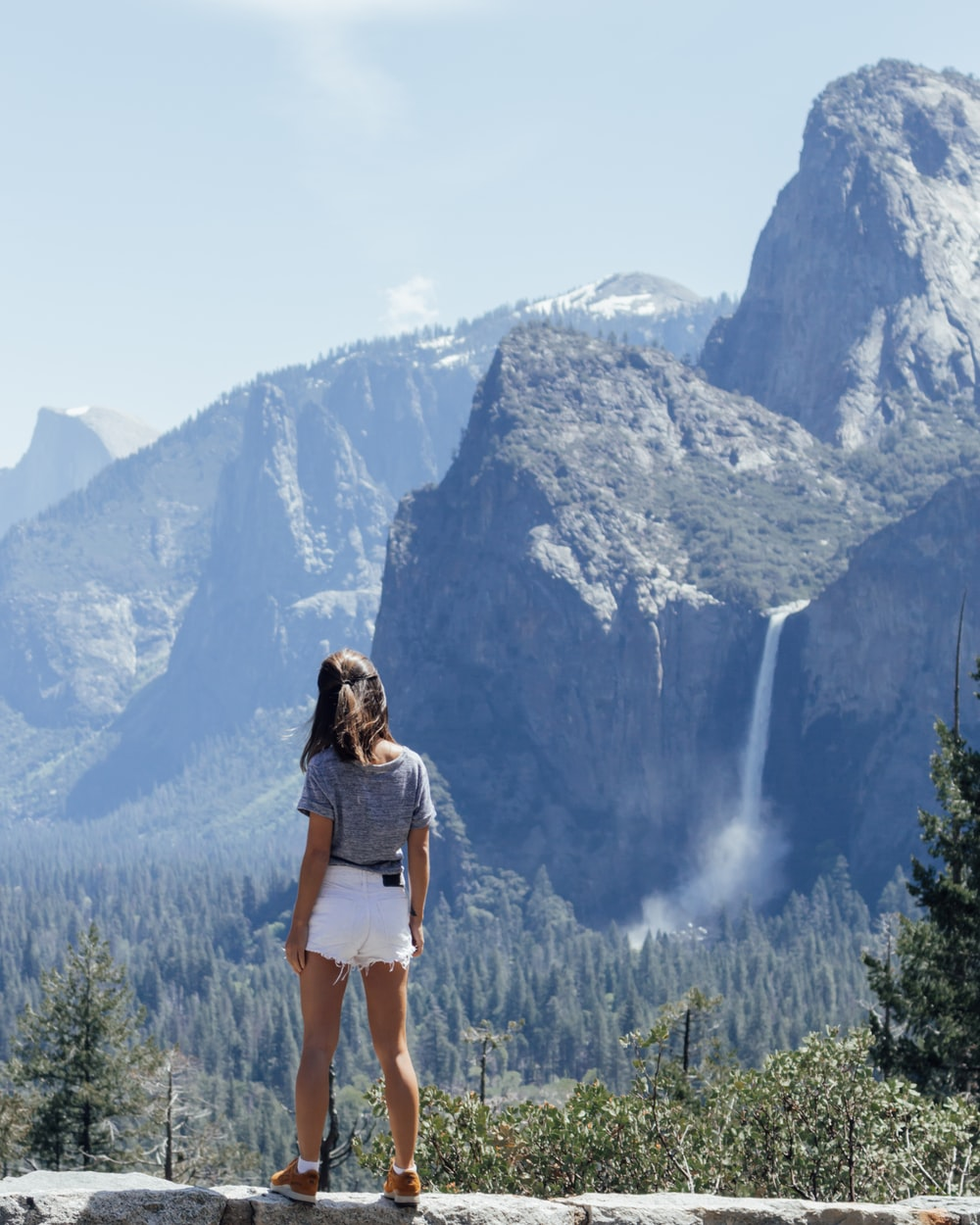 woman wearing blue shirt and white shorts standing beside rocky mountain during daytime