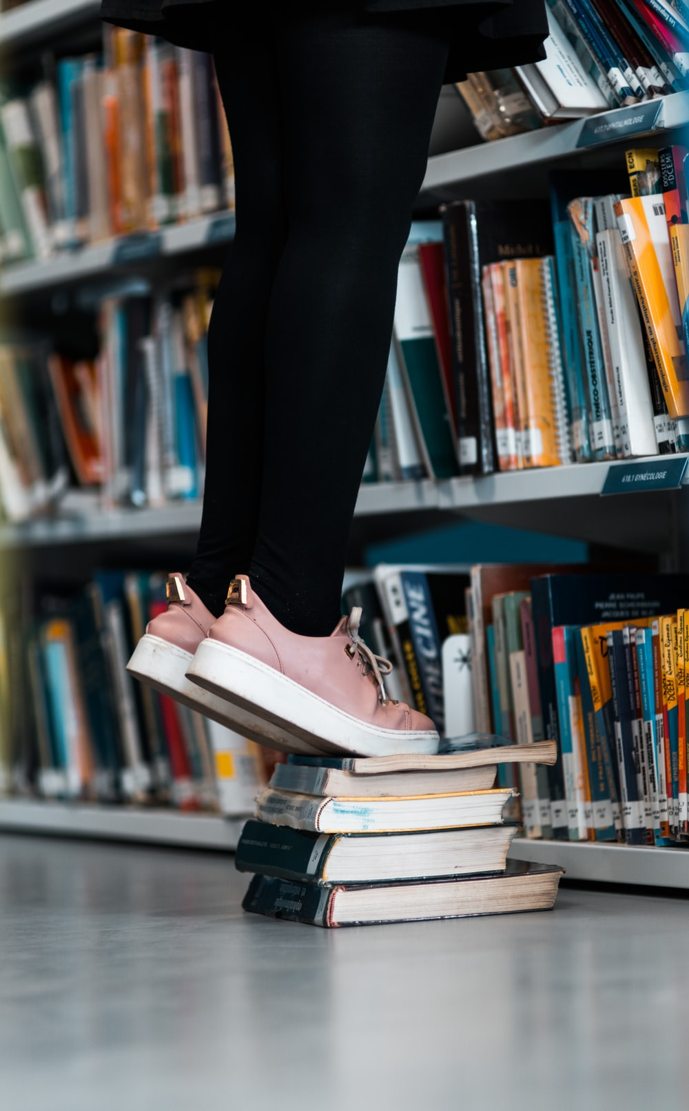 person using books for boosting beside bookcase with books