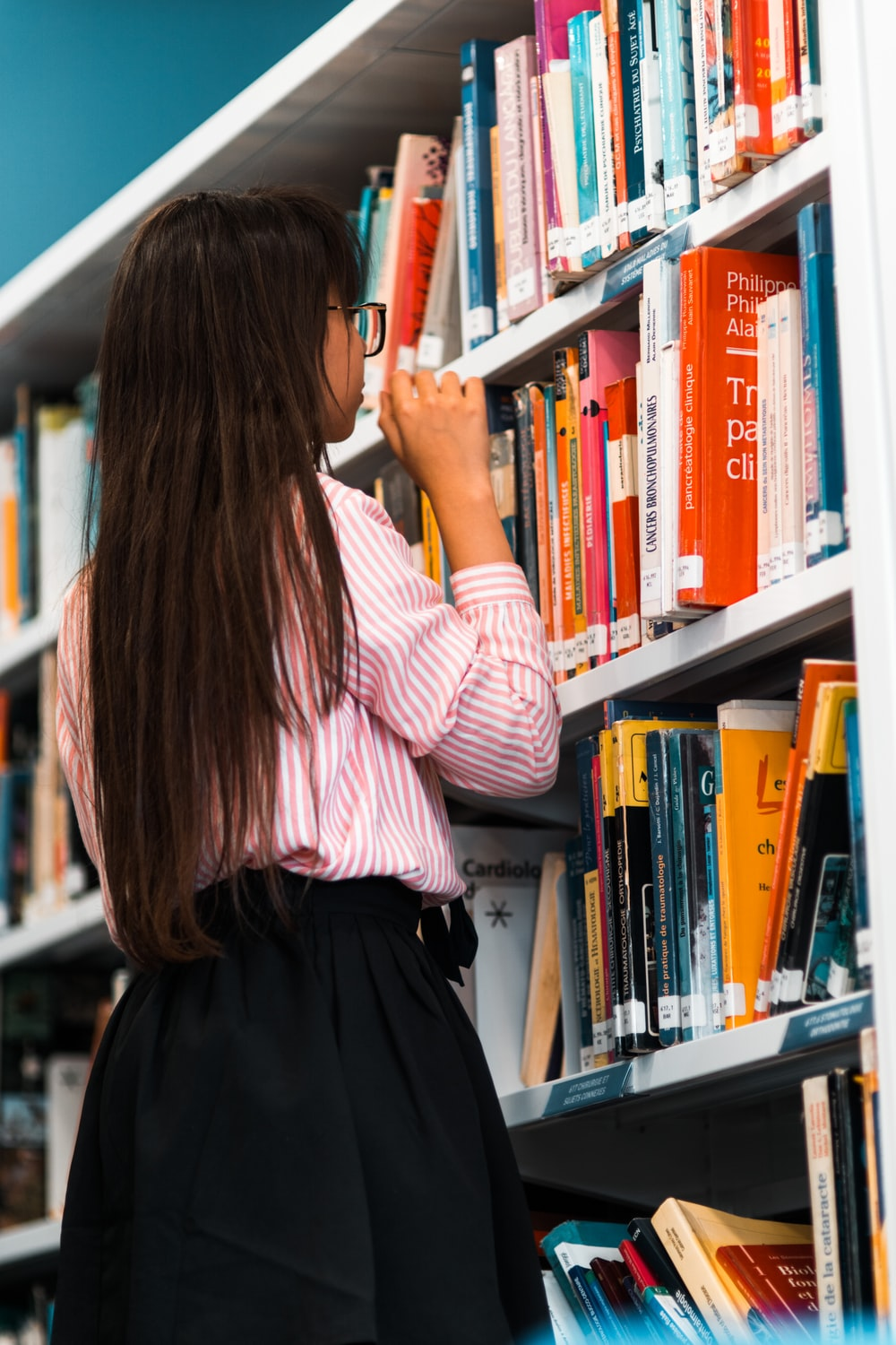 woman wearing pink shirt in front of bookshelf