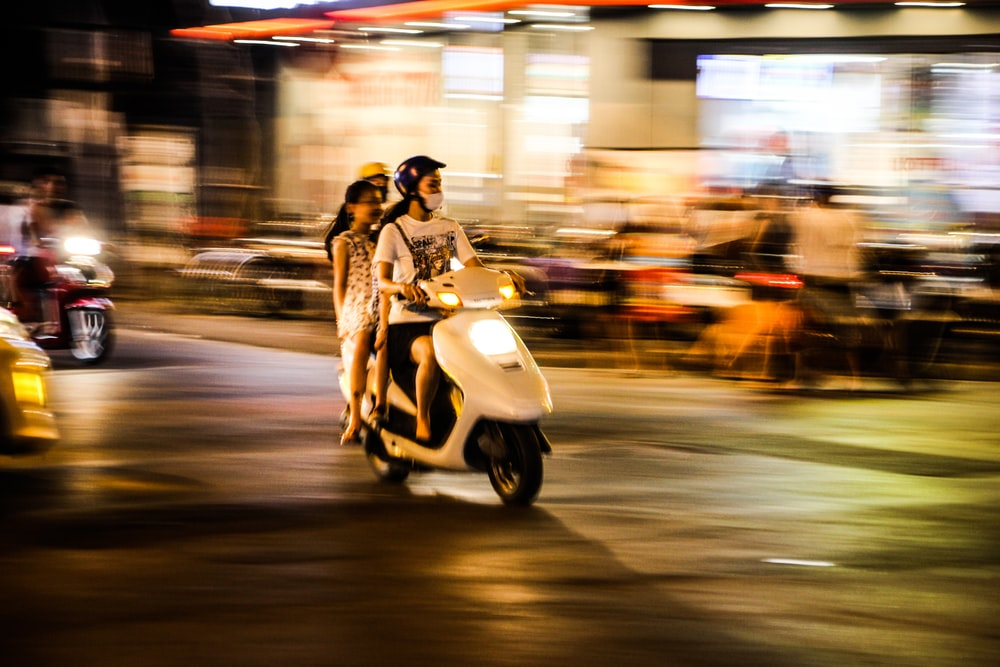 time lapse photography of three people riding a motor scooter