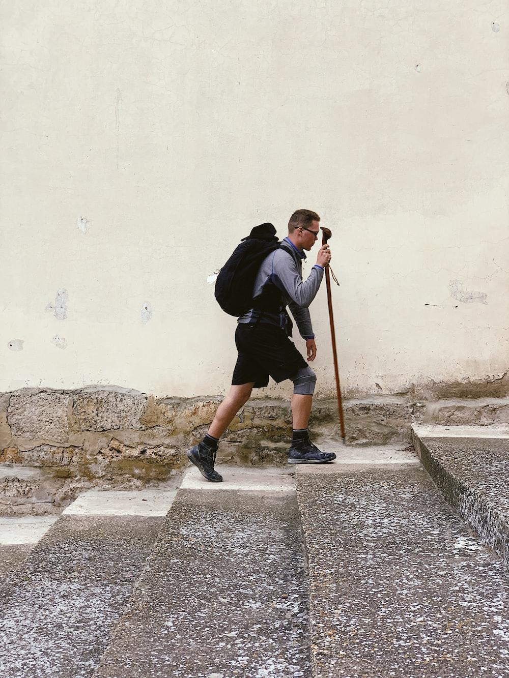 man walking on stairs while holding walking cane