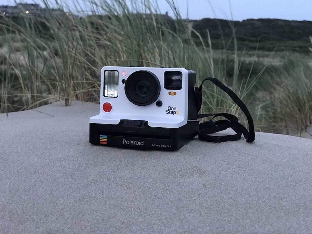white and black Polaroid One Step 2 instant camera
