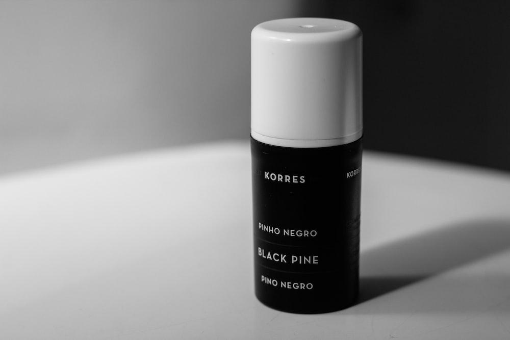 Korres black dine bottle on white surface