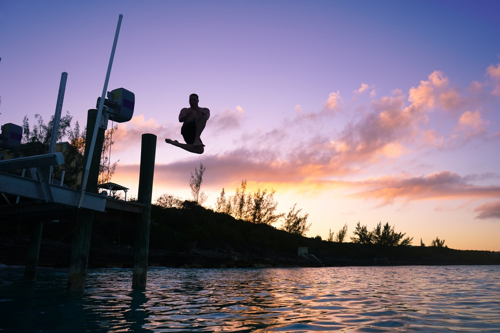 topless man jumping on lake under orange and blue skies