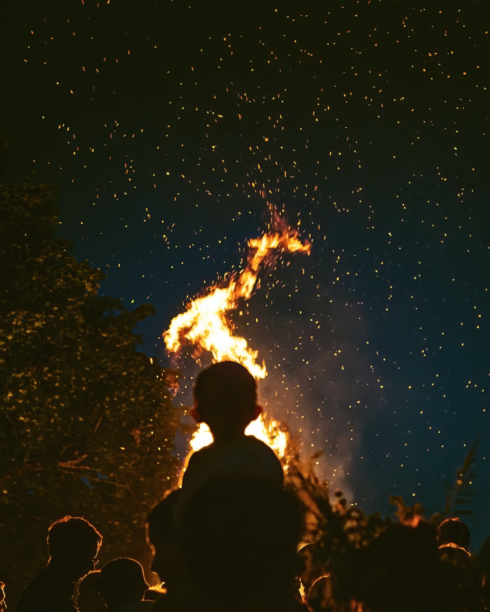 silhouette of people looking on fire under starry night