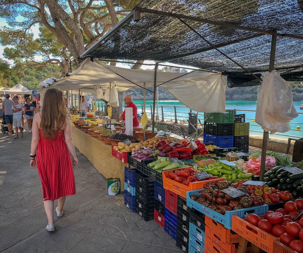 woman walking beside fruit and vegetable vendors