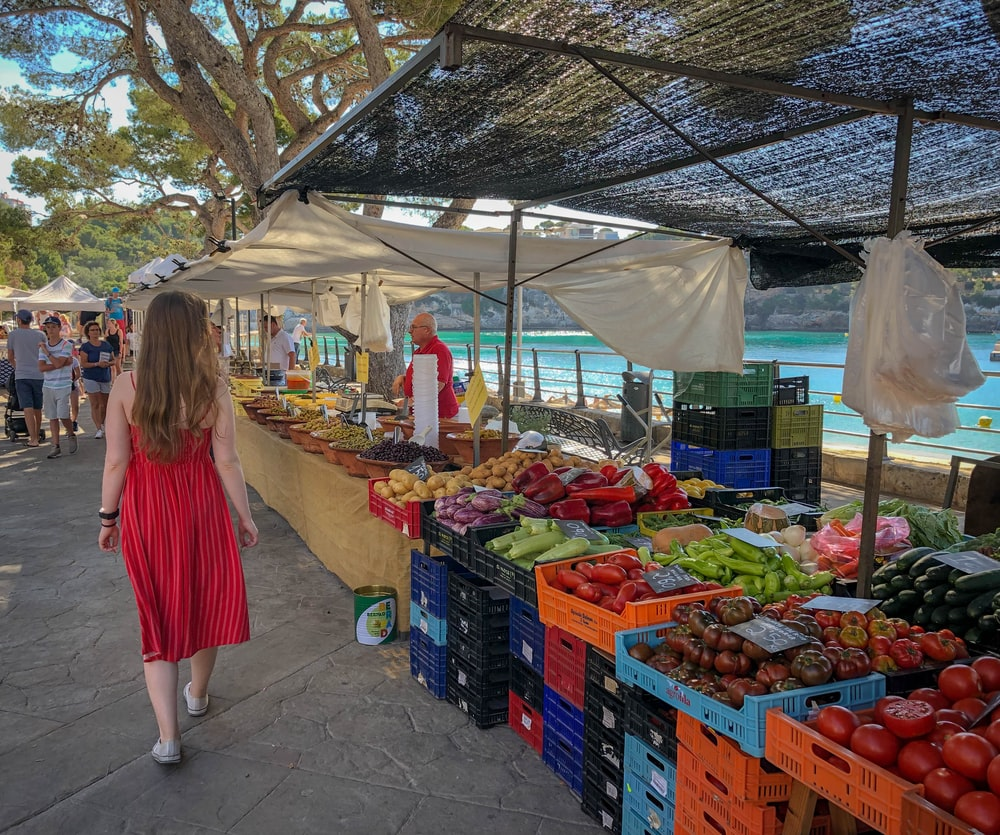 woman walking beside fruit and vegetable vendors