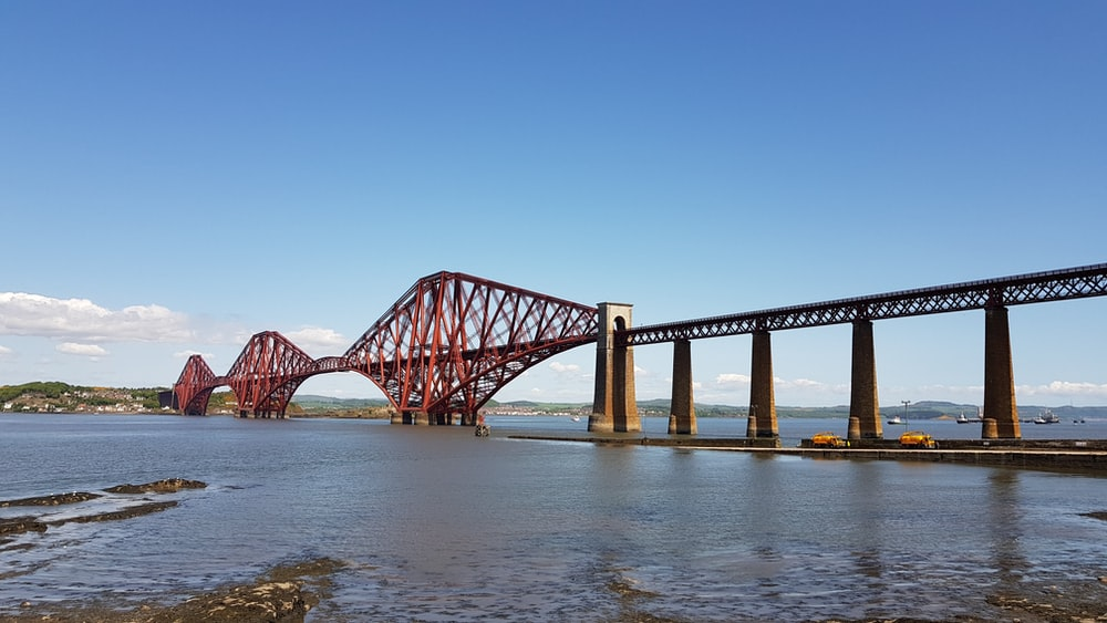 red cable bridge under clear blue sky