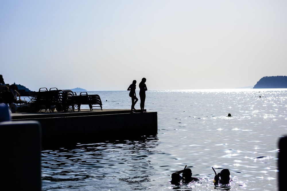 two person standing on dock
