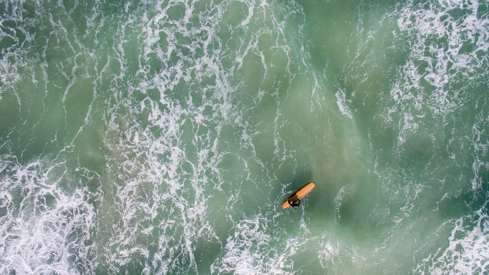 man with brown surfboard at sea