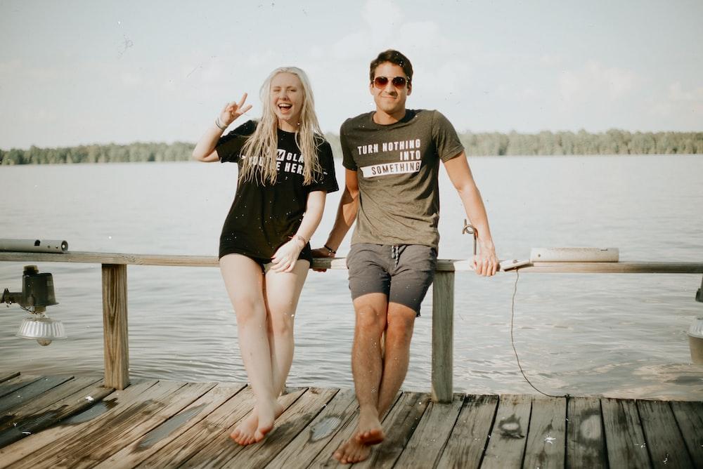 man and woman near calm ocean